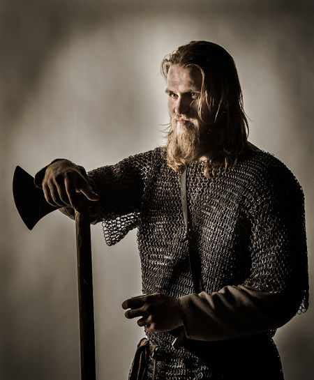 Serious viking with axe standing against wall