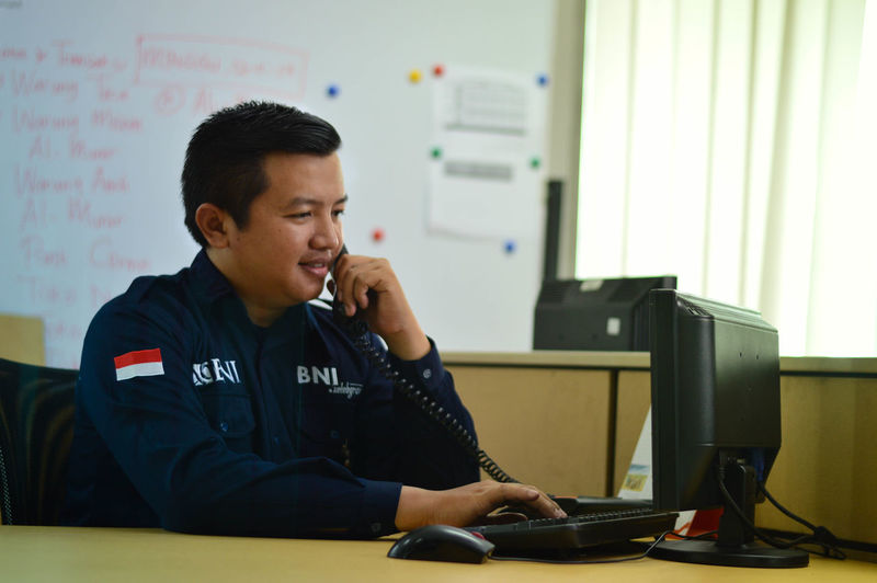 The serving Bni PortraitPhotography Nikonphotography Iamnikon Iamindonesia No_caption_required_pic_says_it_all Photoshoot Dslrphotography EyeEmNewHere Business Stories One Man Only Sitting Computer Indoors  Office Business Finance And Industry Working