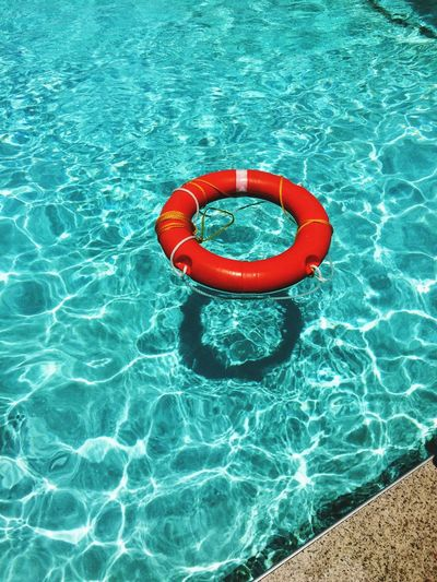 High angle view of red life belt floating on swimming pool
