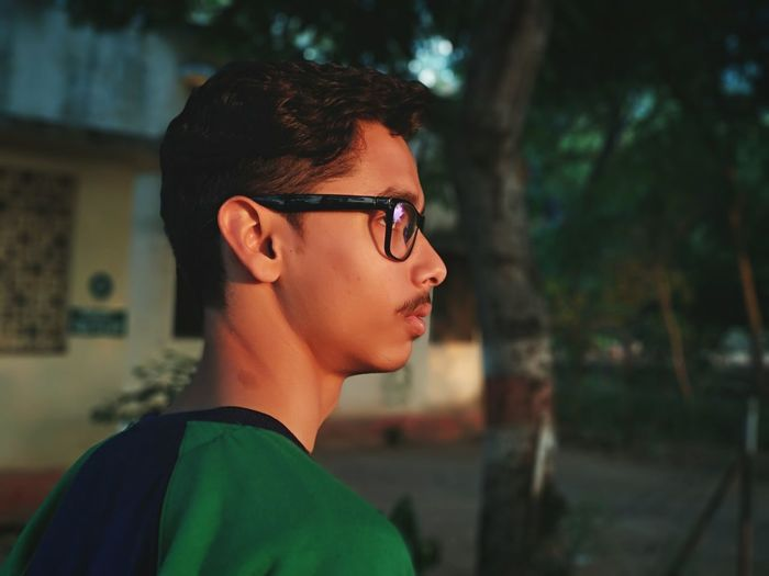 Side view of young man wearing eyeglasses while looking away