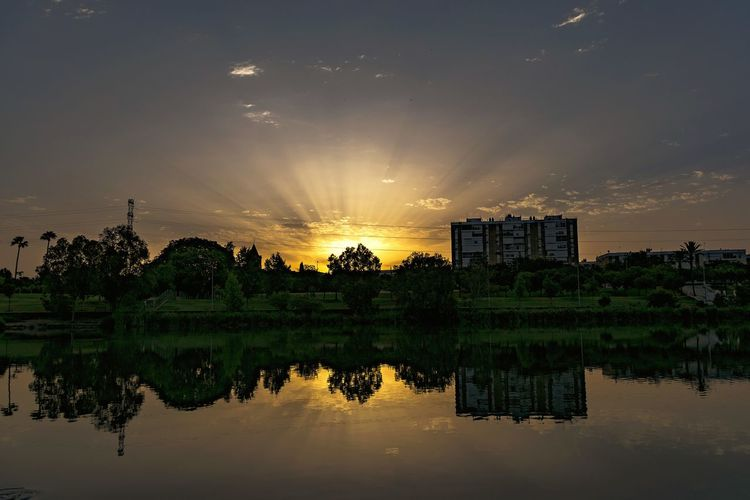 Sunrise River Reflection Water Sky Architecture Nature Cloud - Sky Silhouette Building Sun Sunlight Sunbeam Environment Built Structure Travel Destinations Beauty In Nature Tree Cloudscape Landscape Landscape_Collection Outdoors Beauty Sunrays