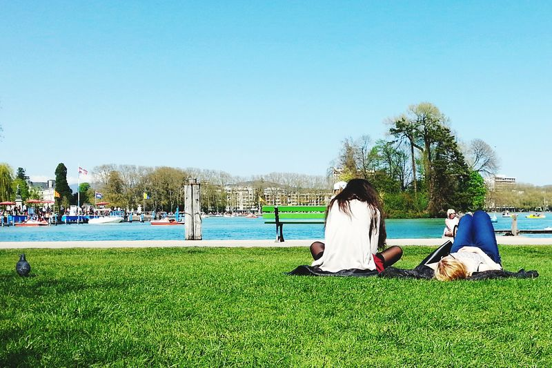 Chilling In The Sun Chilling In The Park Sunny Sunday Afternoon Friendship Laying On Grass In Front Of The Lake Young Women Grass Blue Sky Blue Water People Around You Spring Begins Nice Weather Investing In Quality Of Life