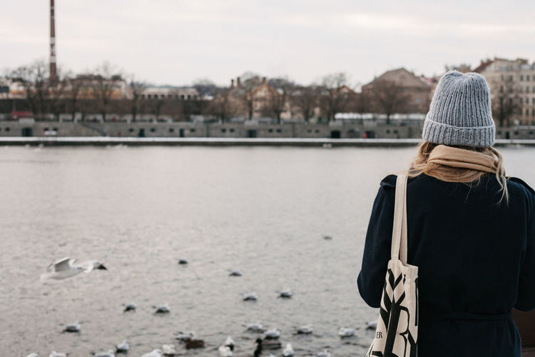 Rear view of woman standing by river against sky during winter