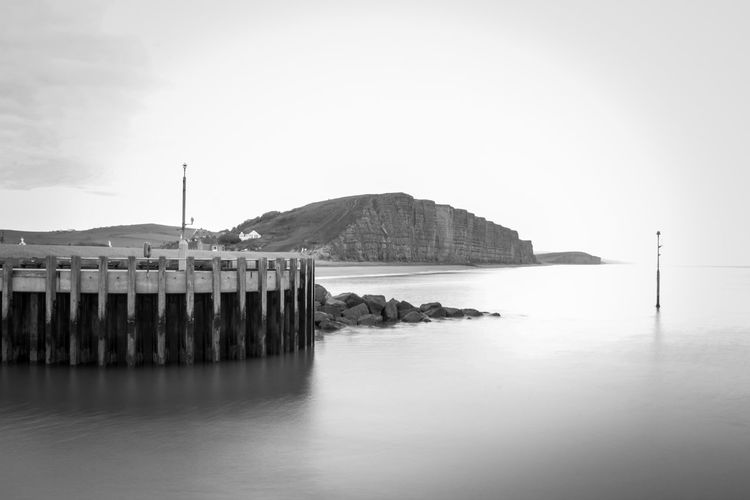 Long Exposure Black And White EyeEm Best Shots EyeEm Nature Lover EyeEmBestPics EyeEm Best Shots - Nature Wonders Of Nature Beauty In Nature Water Sea Harbor Reflection Sky Building Exterior Groyne Wooden Post Horizon Over Water Ocean Seascape Wave Shore Coast Rocky Coastline
