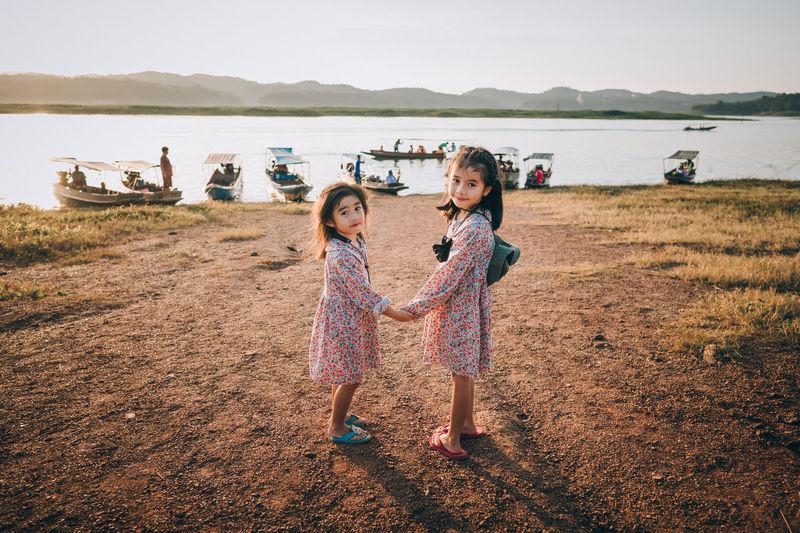 Children standing on field against sky