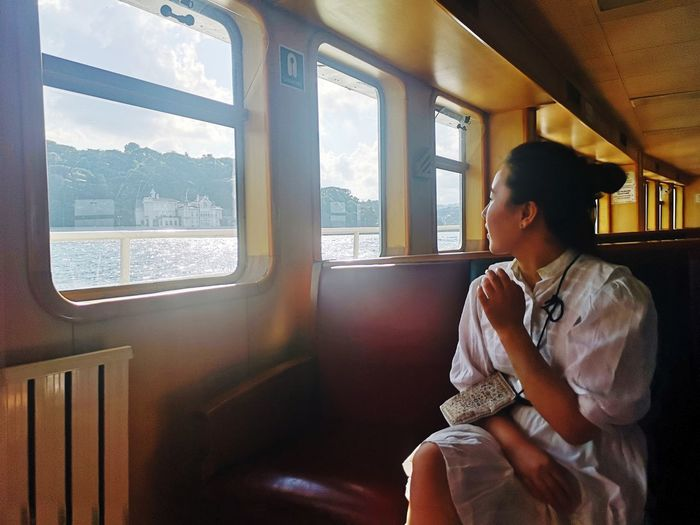 Woman looking through steamboat  window