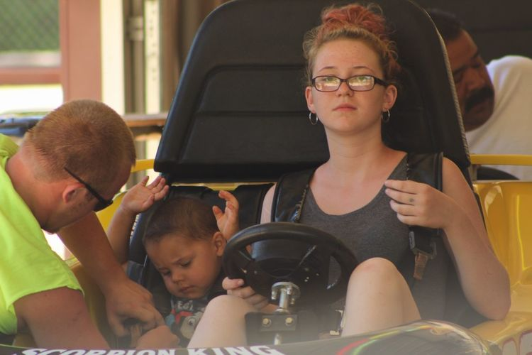 Portrait of mother sitting with son in bumper car at amusement park