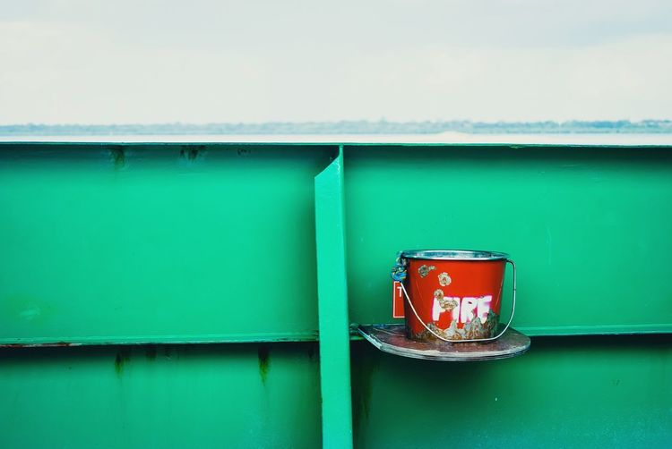 Bucket against green metallic wall
