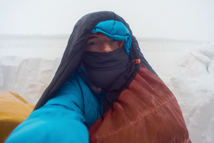 winter camping, hiker taking a selfie in a down jacket and sleeping bag Backpacking Camping Emergency Exploring Extreme Frozen Hiking Man Mountaineering Trekking Winter Adult Adventure Beach Clothing Cold Day Exploration Front View Headscarf Headshot Hood Hood - Clothing Land Leisure Activity Lifestyles Looking At Camera Male Mid Adult One Person Outdoors Portrait Real People Sea Selfie Shelter Sleeping Bag Snow Survival Trek Water