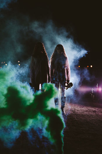 Female friends standing amidst smoke on land at night