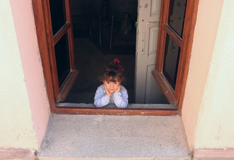 High angle portrait of girl seen through window