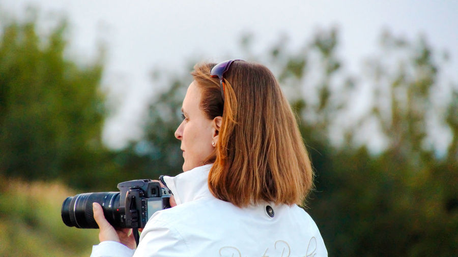 Rear view of woman with dslr against trees