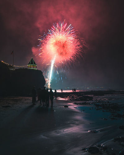 People On Beach Against Firework Display At Night