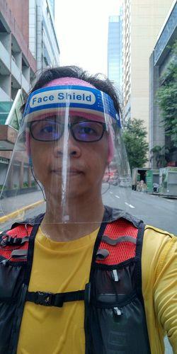 Portrait of man wearing sunglasses on street against buildings in city