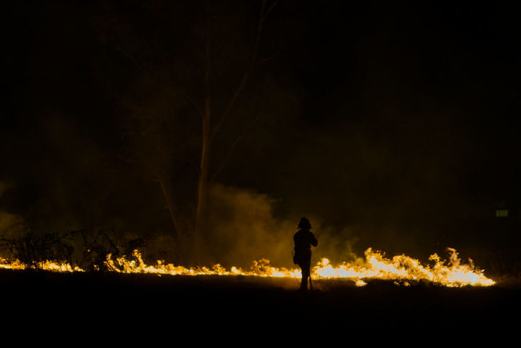 Silhouette of man with fire crackers at night