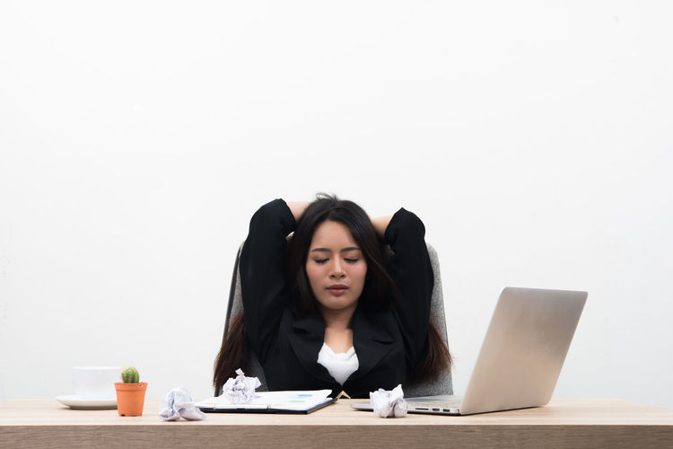 Young Businesswoman With Eyes Closed Sitting By Laptop On Table