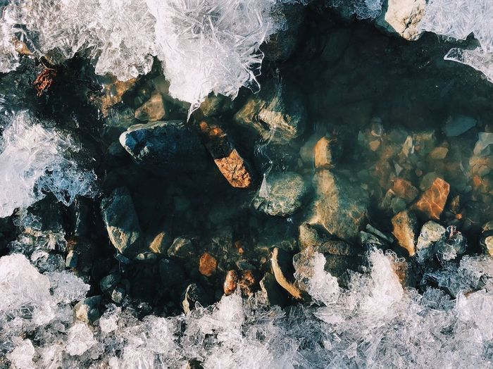 High angle view of rocks in sea during winter