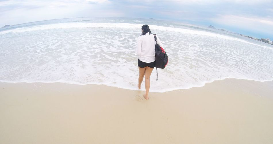 Rear View Of Woman With Backpack Walking At Beach Against Sky