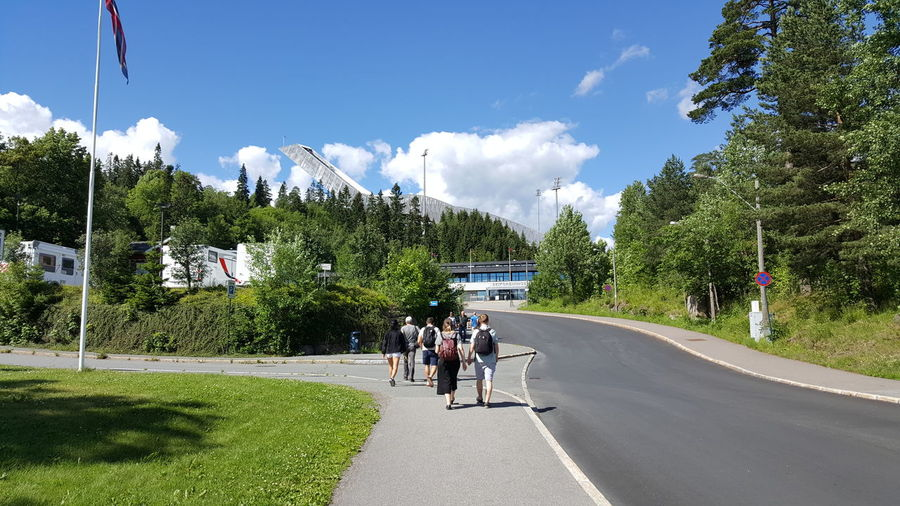 People on road amidst trees against sky