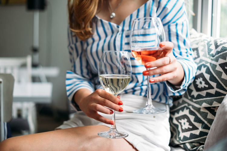 woman holding two glasses of wine Red Wine Stylish Celebration Close-up Day Drink Drinking Glass Food And Drink Holding Home Interior Human Hand Indoors  Lifestyles Real People Togetherness Two People White Wine Wine Wineglass Women Young Adult Young Women