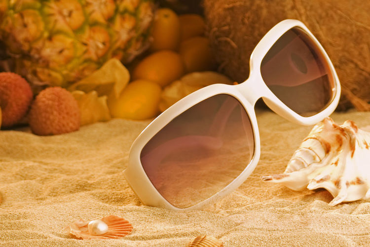 Close-up of sunglasses on sand against fruits