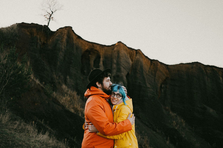 Side view of couple standing on mountain