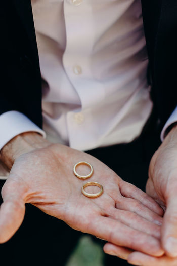 Midsection of bridegroom holding wedding rings