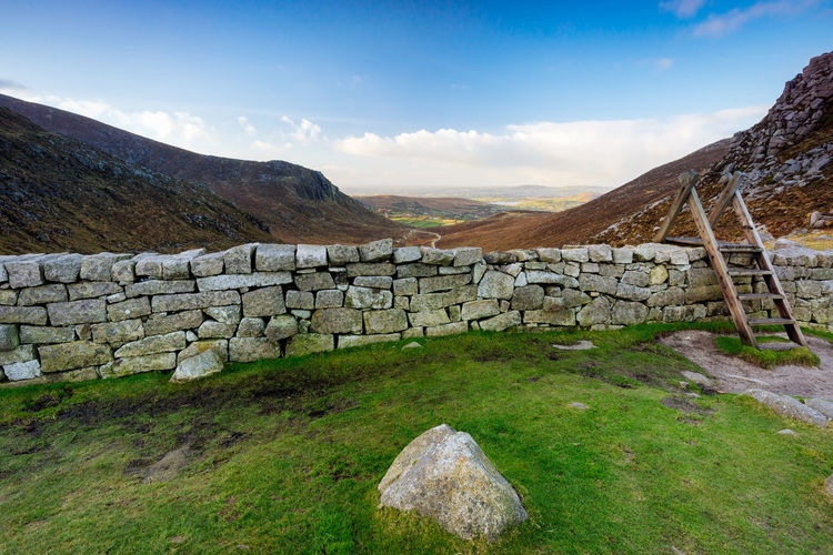 Stone wall by mountain against sky