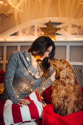 Pets Domestic Domestic Animals Mammal One Animal Real People Dog Canine Vertebrate One Person Three Quarter Length Sitting Home Interior Indoors  Casual Clothing Women Lifestyles Hair Hairstyle Pet Owner