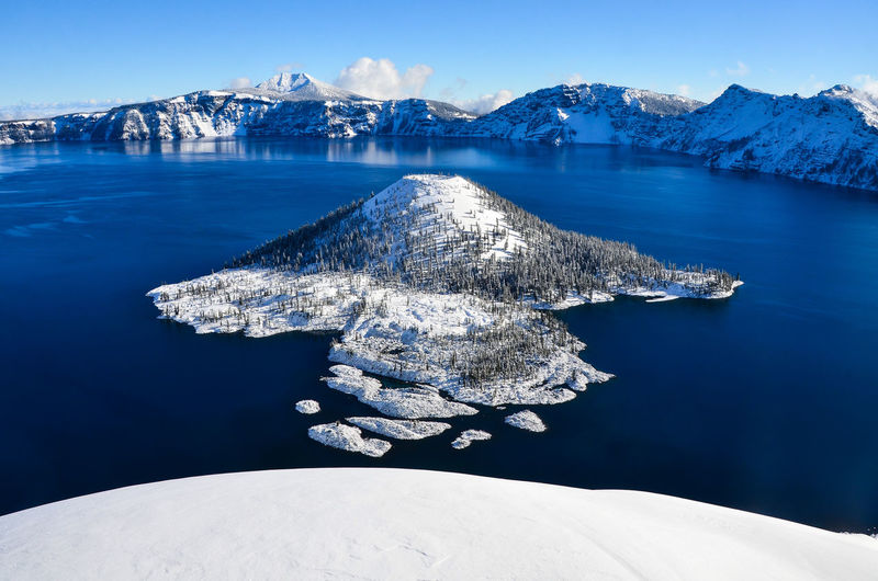 Fresh snow, clear skies, and deep blue water at Crater Lake. In the middle of it all, Wizard Island seems to float on a mirror image of the atmosphere above. Crater Lake National Park Oregon Pacific Northwest  United States Beauty In Nature Blue Clear Sky Cold Temperature Day Mountain National Parks Nature No People Outdoors Scenics Snow Tranquil Scene Water Winter