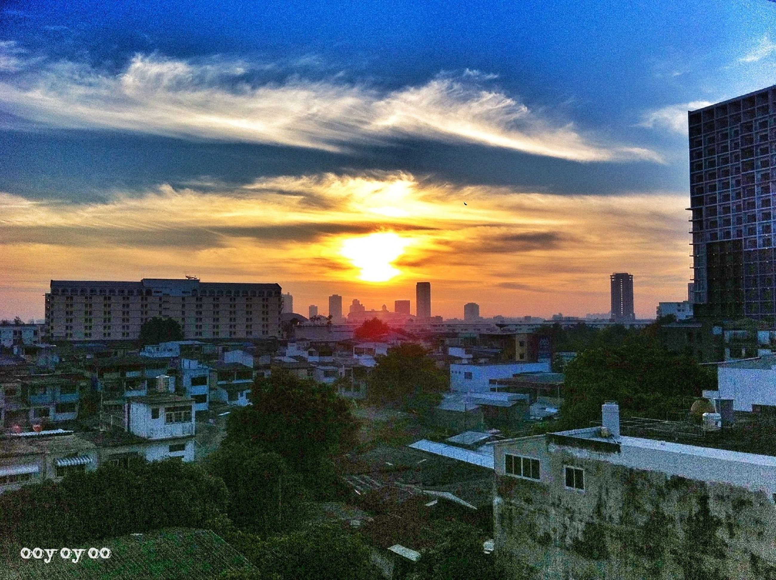 building exterior, architecture, sunset, built structure, city, sky, cityscape, cloud - sky, skyscraper, residential building, sunlight, sun, residential district, residential structure, urban skyline, tower, orange color, building, city life, tree