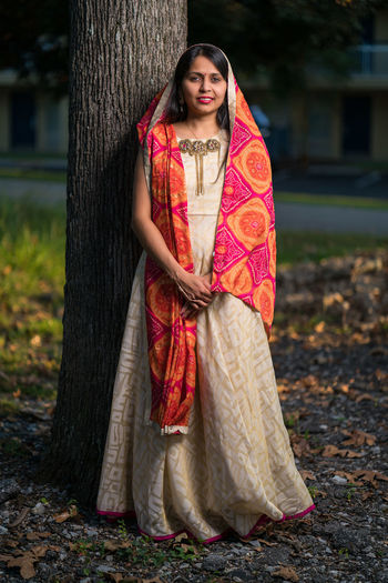 Portrait of young woman in traditional clothing standing against tree trunk