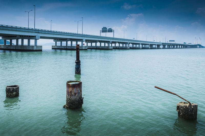 Abandoned metallic posts by bridge over sea against sky