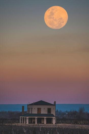 Full frame shot of building against sky during blue hour. full moon.