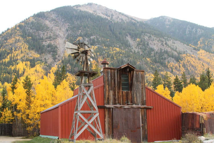 Traditional windmill on field by mountains against sky