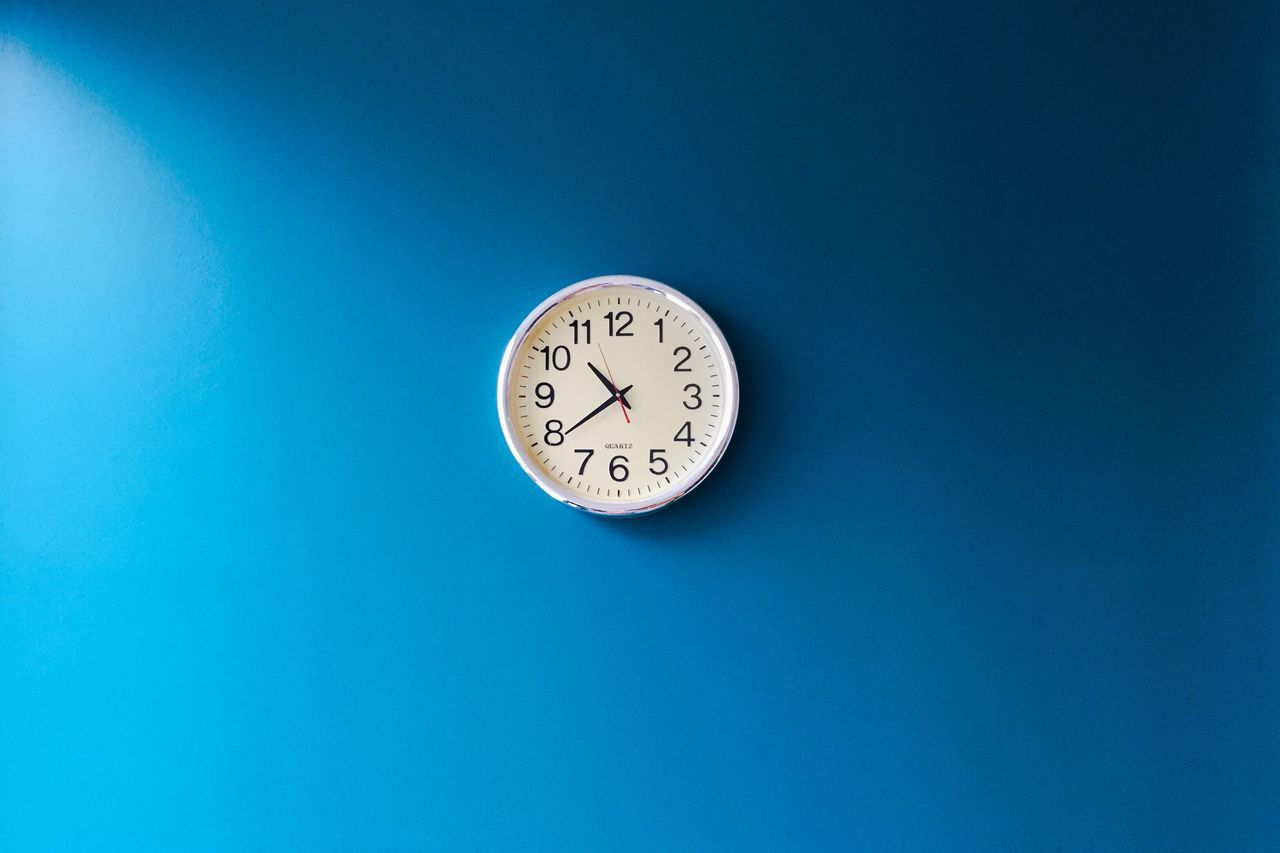 Low angle view of clock against blue background