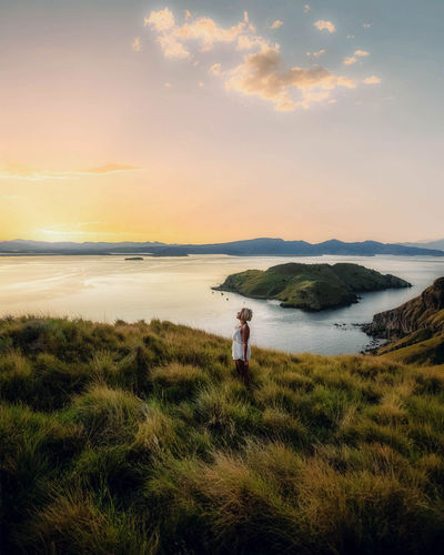Woman standing on field by sea against sky during sunset