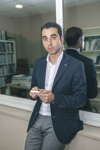Portrait of handsome businessman looking at camera while holding smartphone Business Busy Company Man Suit Working Business Finance And Industry Businessman Caucasian Chairman Chief Concentration Device Executive  Headquarters Jacket Job Male One Person Portrait Serious Smart Phone Sucess Technology Vertical