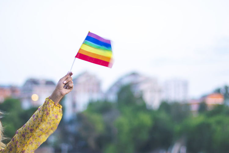 Cropped hand of woman holding rainbow flag against sky