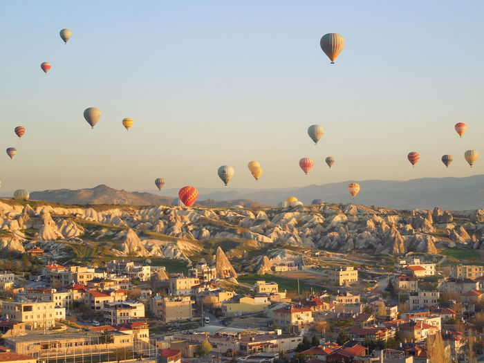 Hot air balloons flying over buildings in cappdocia
