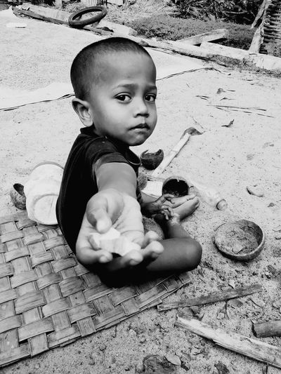 Portrait of cute boy giving food while sitting on floor