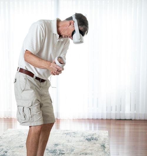 Man holding camera while standing at home
