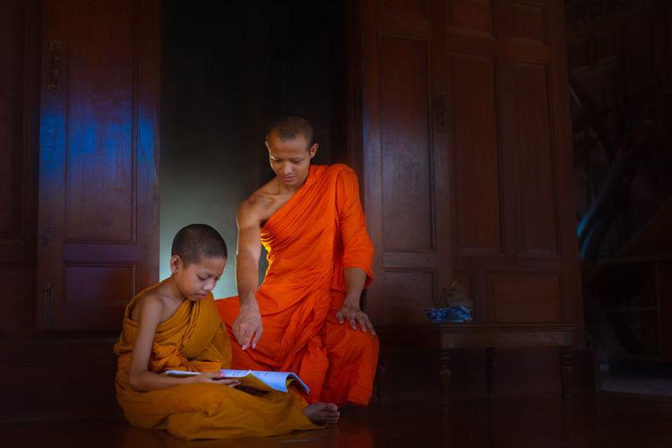 Monk teaching boy in monastery