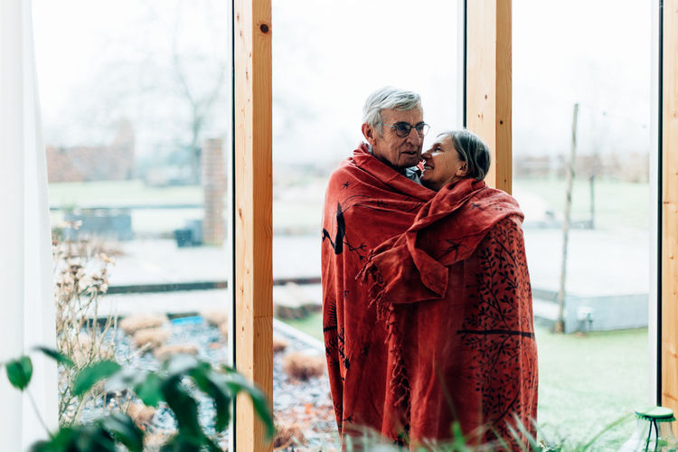 Cheerful and smiling older couple wrapped in a blanket at home standing at the window