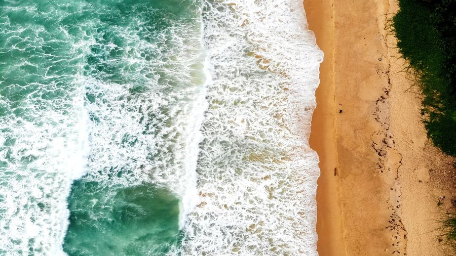 Aerial View Of Sea Waves Splashing At Beach