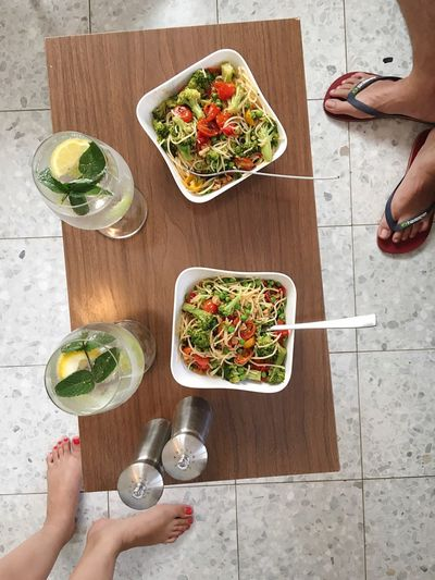Low section of couple standing by noodles and lemonades on wooden table at floor