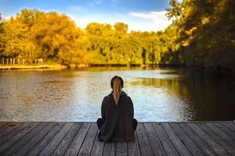 Young woman sitting on jetty by lake against sky