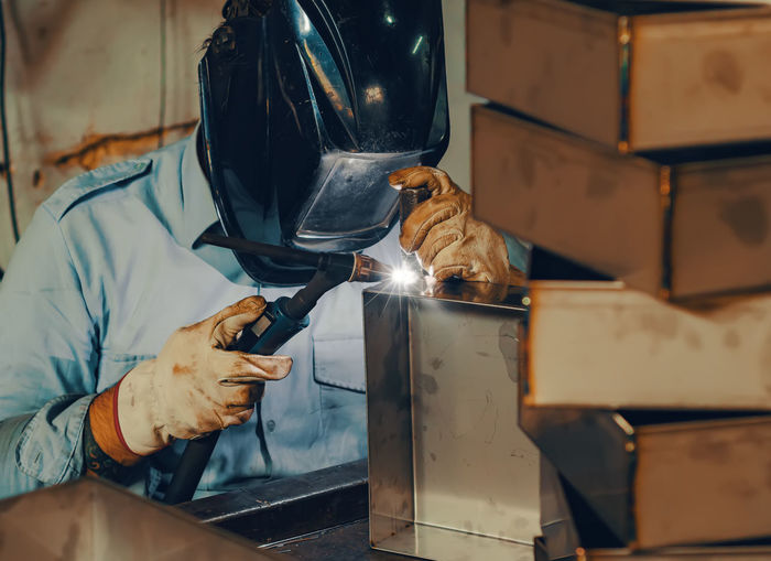 Welder welds a metal box.