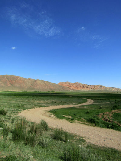 A winding road from Balykchy to Kochkor, Kyrgyzstan. Balykchy Kyrgyzstan Road Tranquility Beauty In Nature Blue Day Field Grass Kochkor Landscape Mountains Nature No People Outdoors Scenics Sky Tranquil Scene Winding Road