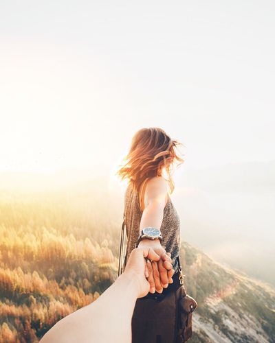 Woman Holding Hand On Mountain Against Sky During Sunset